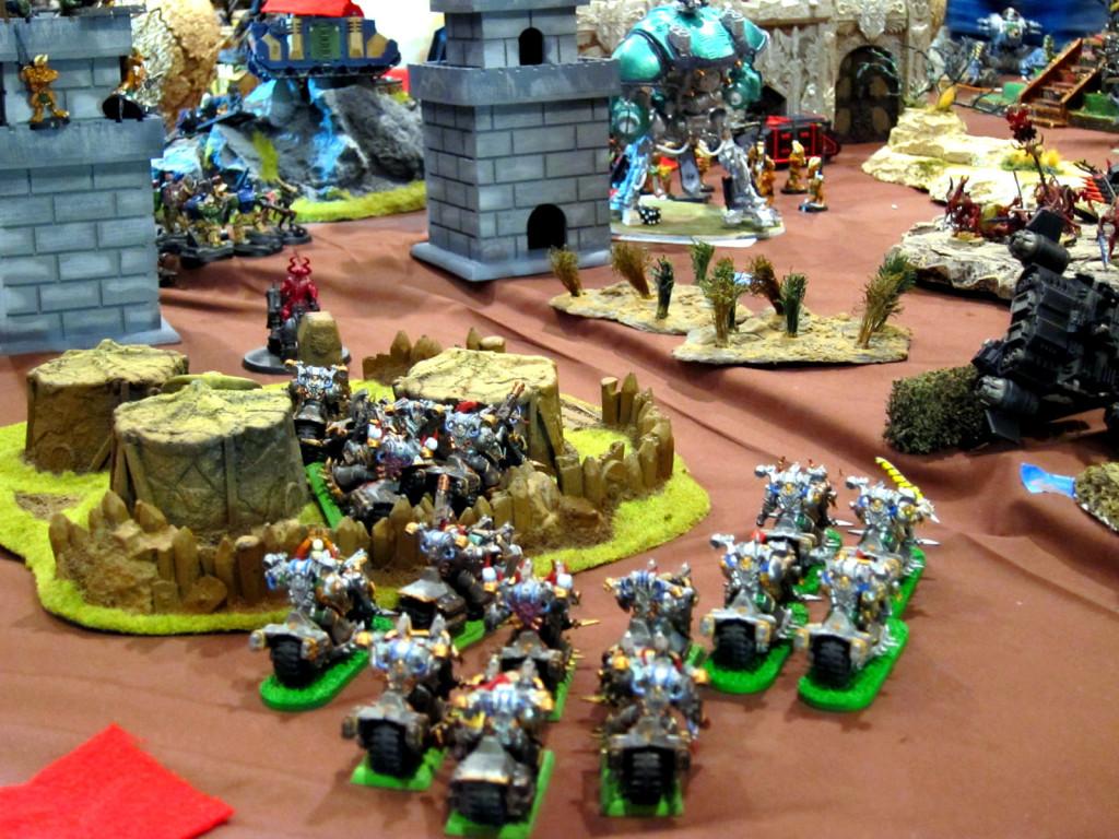 Traitor melta-bikers race through a slave village toward a Knight Errant threatening their perimeter bastions.