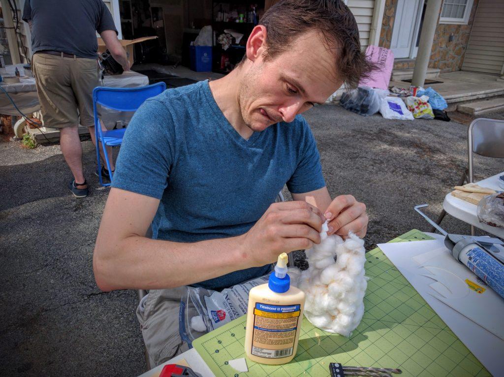Alex gluing cotton balls into rough positions to start the smoke column.