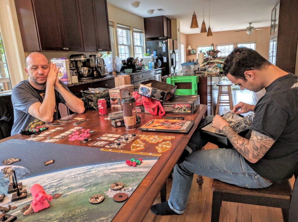 Matt ponders game balance as he watches a VIP Escort playtest, while Jason stays firmly focused on the grimdark.